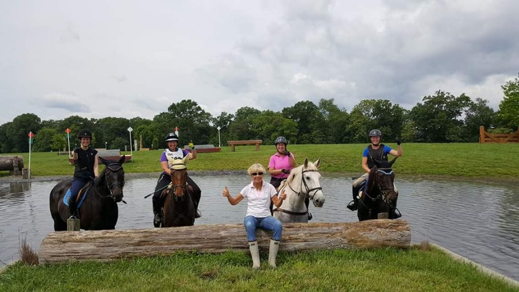 Lisa Reid with four students Eventing at a water complex on a cross country course